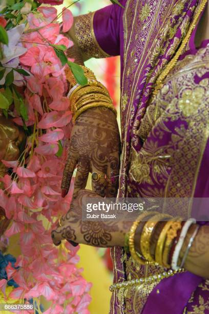 Close up of hands with intricate henna design and Wedding jewellery.