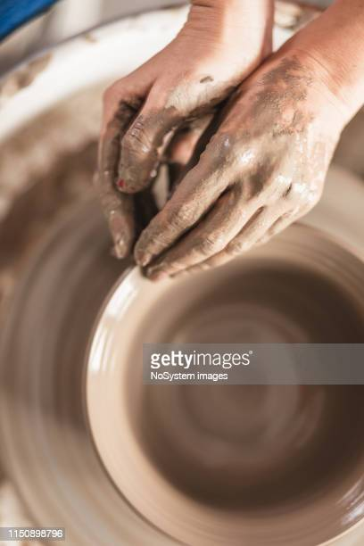 close up of hands working on pottery wheel - potter stock pictures, royalty-free photos & images