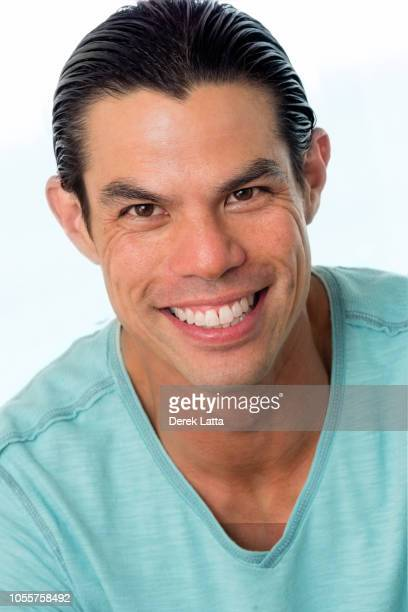 Close up of handsome Asian American man on white background smiling'n