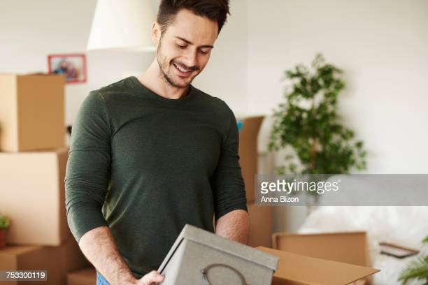 Close up of handsome man opening moving boxes. Debica, Poland