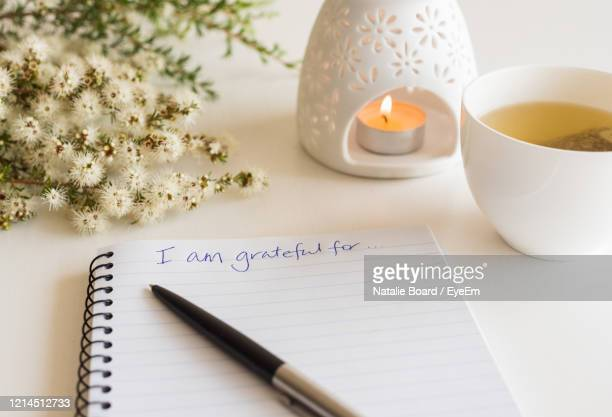 close up of handwritten gratitude text with notebook, pen, cup of tea, flowers and oil burner l - gratitude stock pictures, royalty-free photos & images