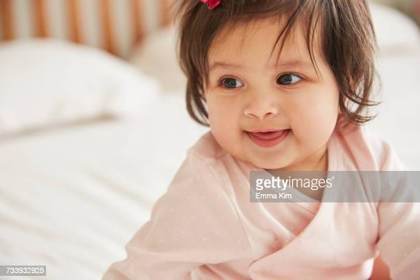 close up of happy baby girl sitting up on bed - baby girls stock photos and pictures