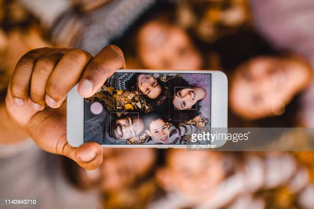 close up of happy black family taking a selfie with cell phone in autumn leaves. - selfie stock pictures, royalty-free photos & images