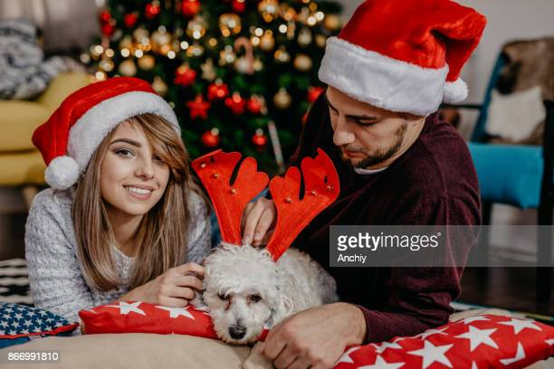 Close up of happy couple with the dog in between, new year's eve concept
