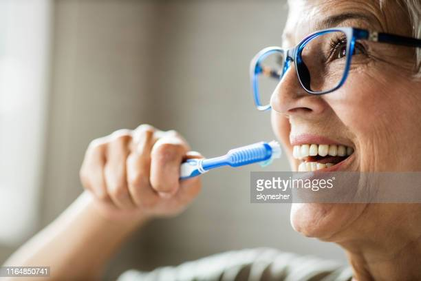close up of happy senior woman brushing her teeth. - human teeth stock pictures, royalty-free photos & images