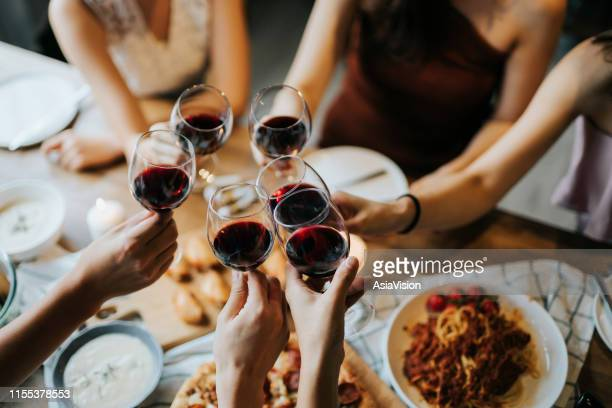 close up of happy young friends having fun and toasting and celebrating with red wine during party - honour stock pictures, royalty-free photos & images