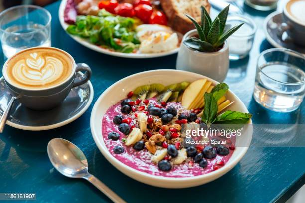 close up of healthy breakfast with acai bowl, fresh berries and fruits - kaffee getränk stock-fotos und bilder