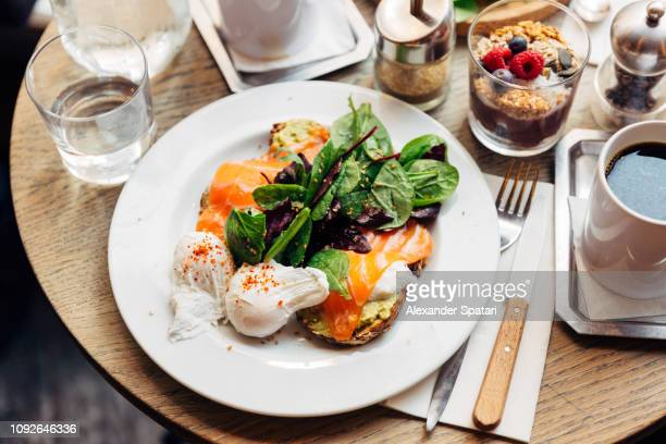 close up of healthy breakfast with avocado on toast, poached egg and spinach - hotel breakfast stock pictures, royalty-free photos & images