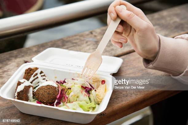 Close up of healthy food in take away box, hand holding fork at urban market.