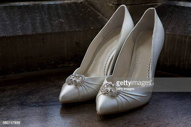 close up of high heeled wedding shoes. - white satin stock photos and pictures