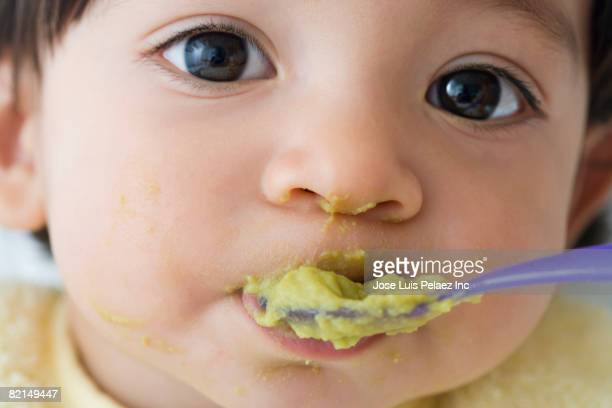 Close up of Hispanic baby being fed