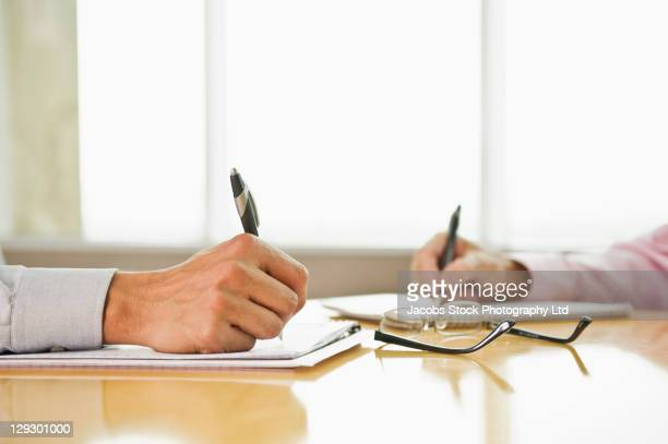 close up of hispanic businessmen's hand writing in notebooks - sells arizona stock pictures, royalty-free photos & images