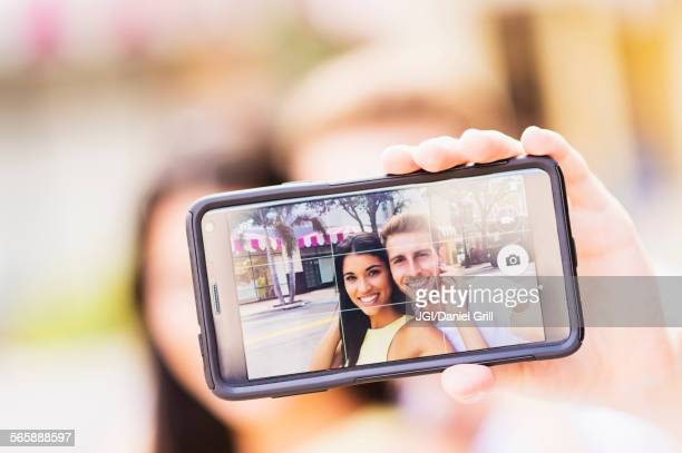 Close up of Hispanic couple taking selfie outdoors