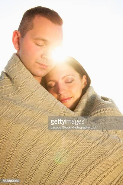 Close up of Hispanic couple wrapped in blanket
