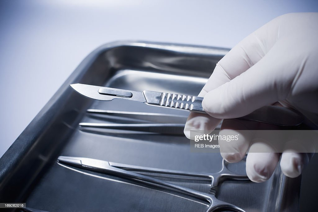 Close up of Hispanic doctor holding surgical equipment : Stock Photo