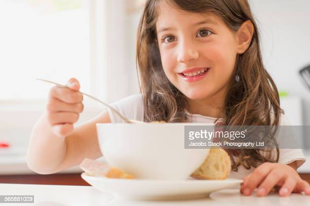 Close up of Hispanic girl eating bowl of soup