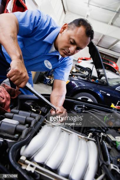 Close up of Hispanic male auto mechanic working on engine in auto repair shop