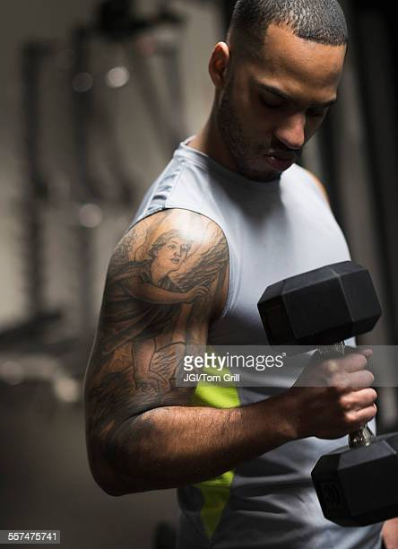 Close up of Hispanic man lifting weights in gym
