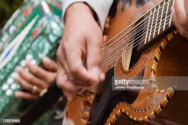 Close up of Hispanic man playing guitar