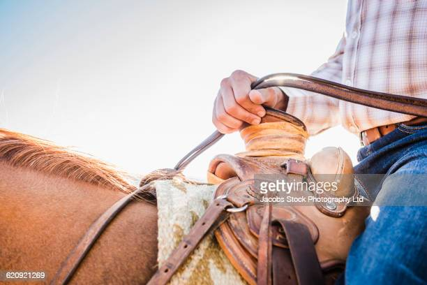 close up of hispanic man riding horse - rein stock pictures, royalty-free photos & images