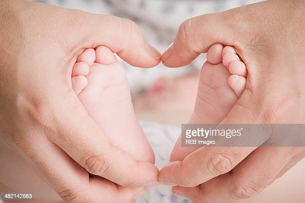Close up of Hispanic mother cupping baby boy's feet