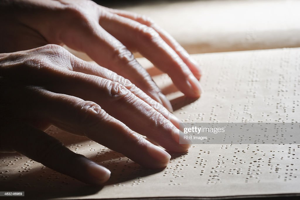 Close up of Hispanic person reading Braille : Stock Photo