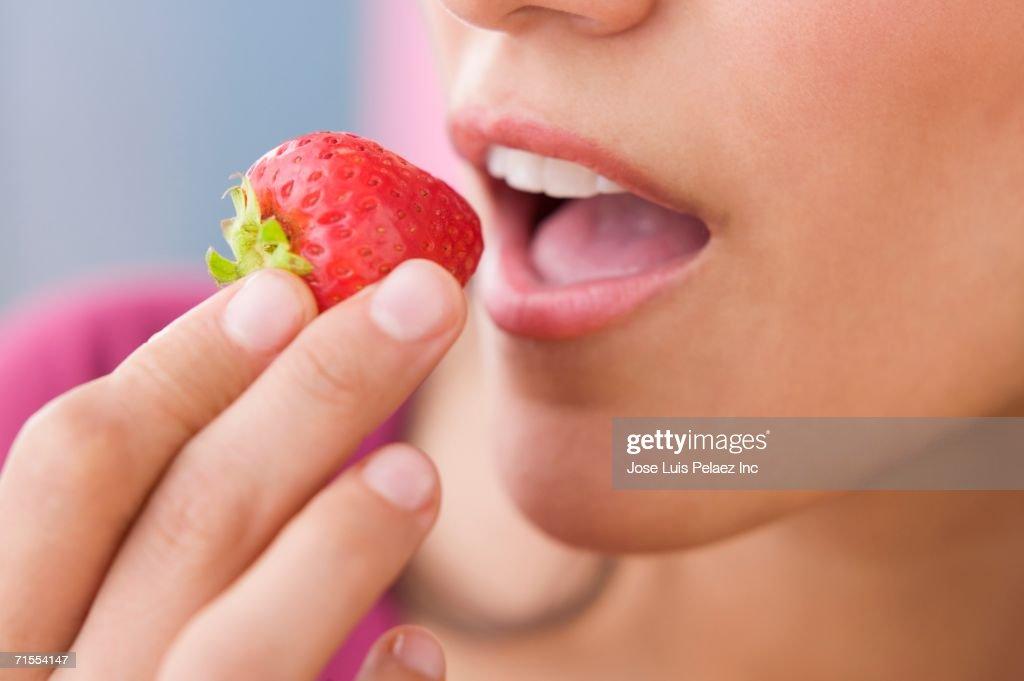 Close up of Hispanic woman eating strawberry : Stock Photo