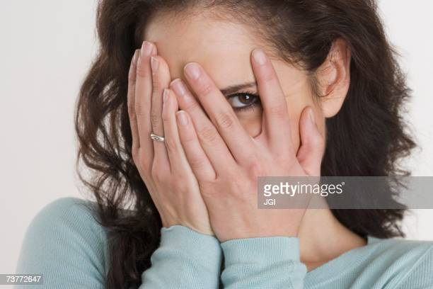 close up of hispanic woman peeking through fingers - head in hands stock pictures, royalty-free photos & images