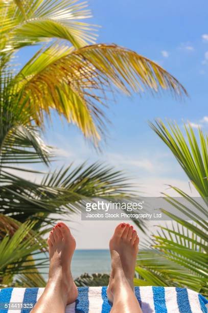 Close up of Hispanic woman's feet on tropical beach