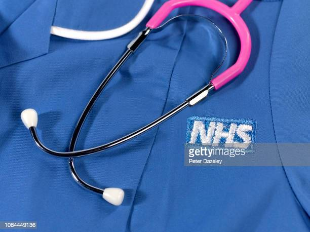 close up of hospital uniform with stethoscope and the National Health Service logo
