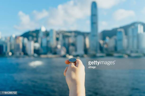 close up of human hand holding coin and getting ready to flip against hong kong cityscape and victoria harbour on a sunny day - flipping a coin stock pictures, royalty-free photos & images