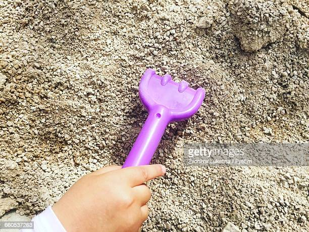 Close Up Of Human Hand Raking Sand With Toy