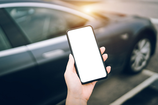 Close up of human hand using smartphone against black car in city - gettyimageskorea