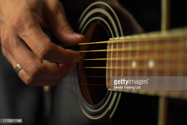 close up of human hands and part of guitar - folk music stock pictures, royalty-free photos & images