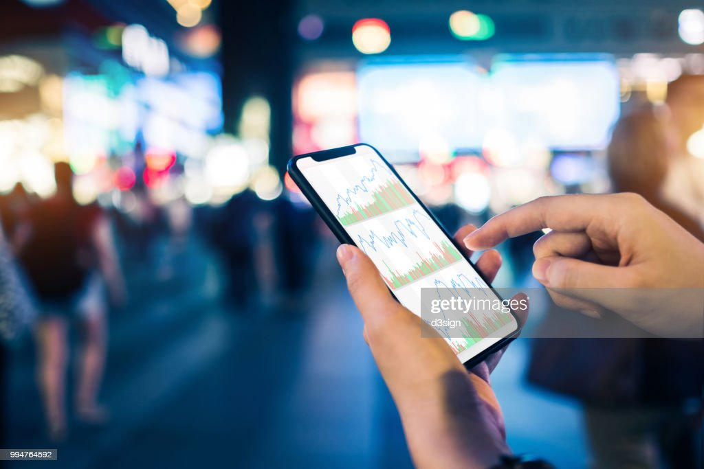 Close up of human hands checking financial stock charts on smartphone in busy city street, against neon commercial sign at night : Stockfoto