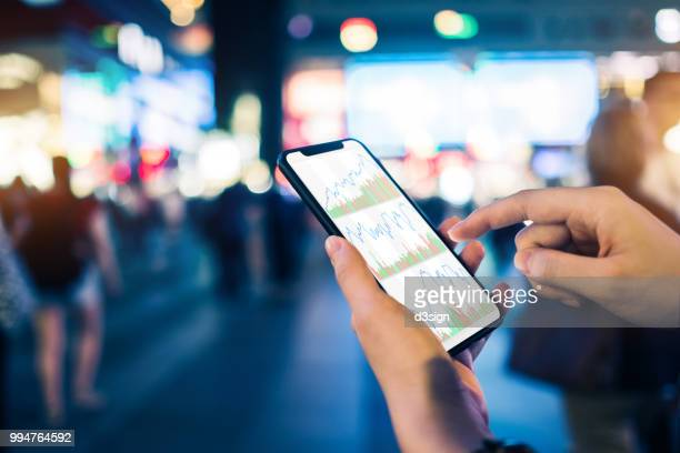close up of human hands checking financial stock charts on smartphone in busy city street, against neon commercial sign at night - elektronische organiser stockfoto's en -beelden