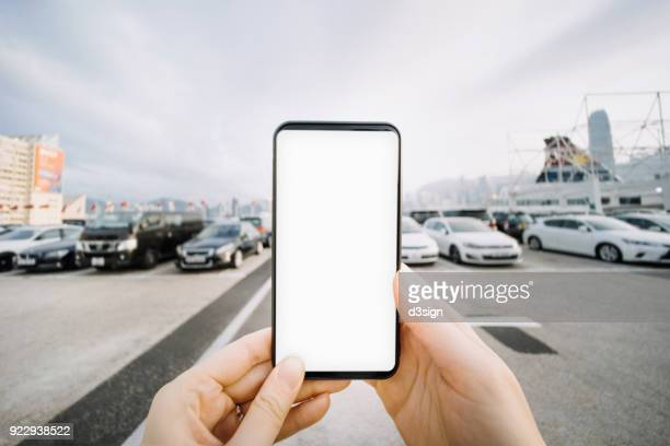 close up of human hands using smartphone outdoors against parking lot and cityscape - convenience stock photos and pictures
