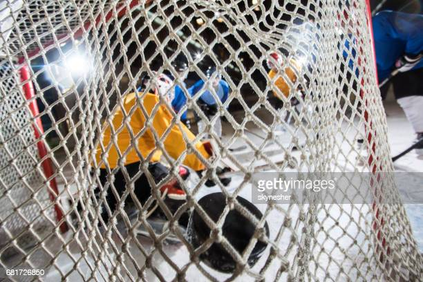 Close up of ice hockey goalkeeper's net with hockey puck in it.