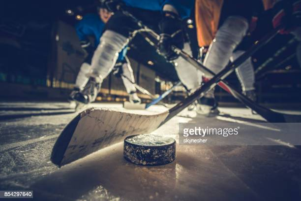 close up of ice hockey puck and stick during a match. - hockey foto e immagini stock