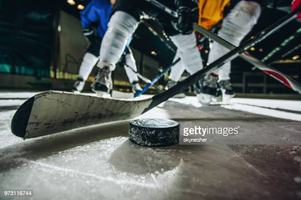 close up of ice hockey puck and stick during a match. - ice hockey stock pictures, royalty-free photos & images