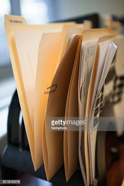 close up of inbox row of files on office desk - heshphoto photos et images de collection