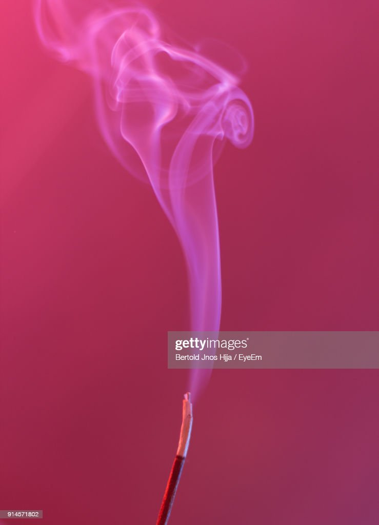 Close Up Of Incense Emitting Smoke Against Pink Wall : Stock Photo