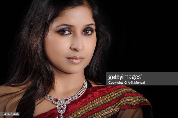 Close up of Indian woman portrait with diamond necklace, black sari black background copy space