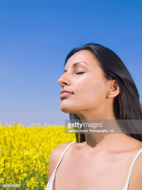 Close up of Indian woman with eyes closed in field of flowers