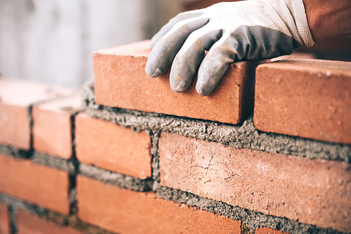 Close up of industrial bricklayer installing bricks on construction site 622800884