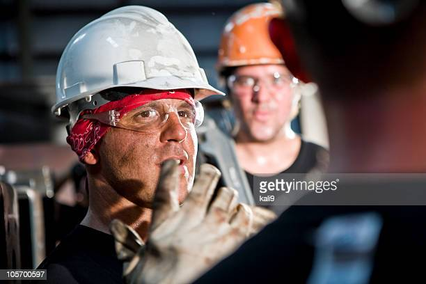 Close up of industrial foreman conversing in factory