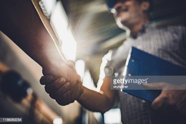 close up of inspector shaking hands with unrecognizable person in a factory. - trust stock pictures, royalty-free photos & images