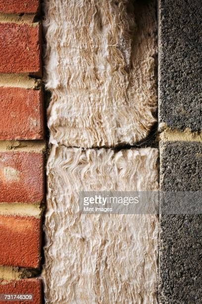 Close up of insulation between a brick and cinder block wall.