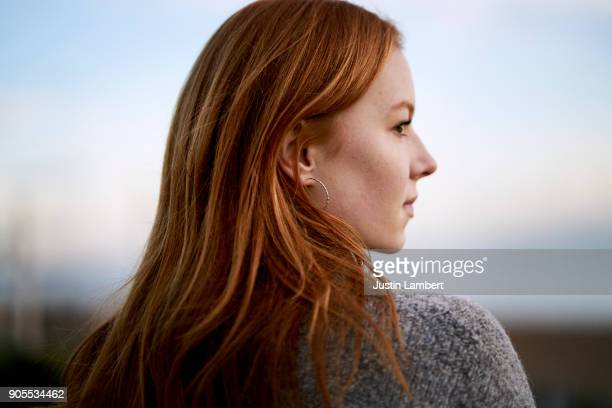 close up of intense red hair of teenager looking out to sea on a beach in winter - soft focus stock pictures, royalty-free photos & images