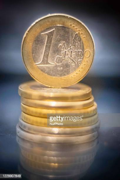 Close up of isolated one Euro coin the main currency of the European Union, money stacked on euro coins in the background on a reflecting surface....